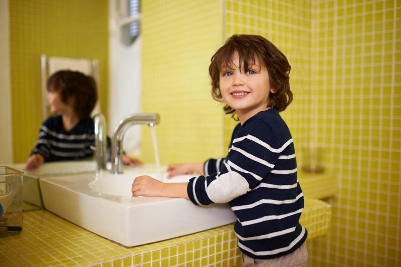 chłopiec myje ręce w przedszkolu